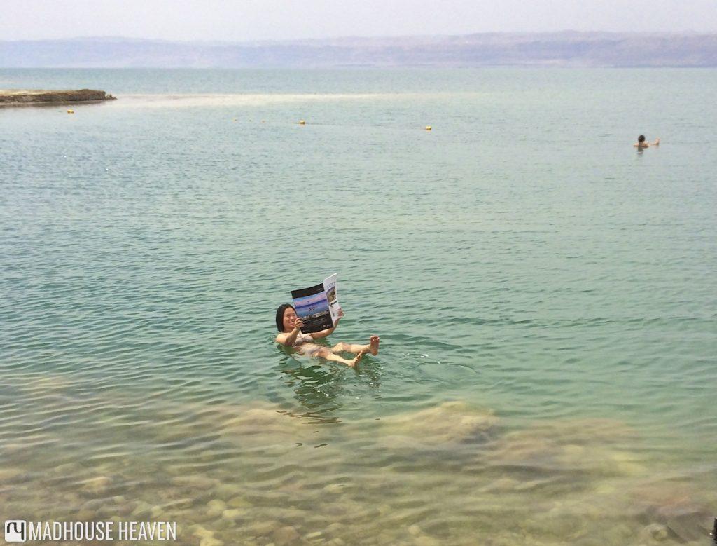 floating dead sea, reading in the dead sea, jordan, kempinski hotel