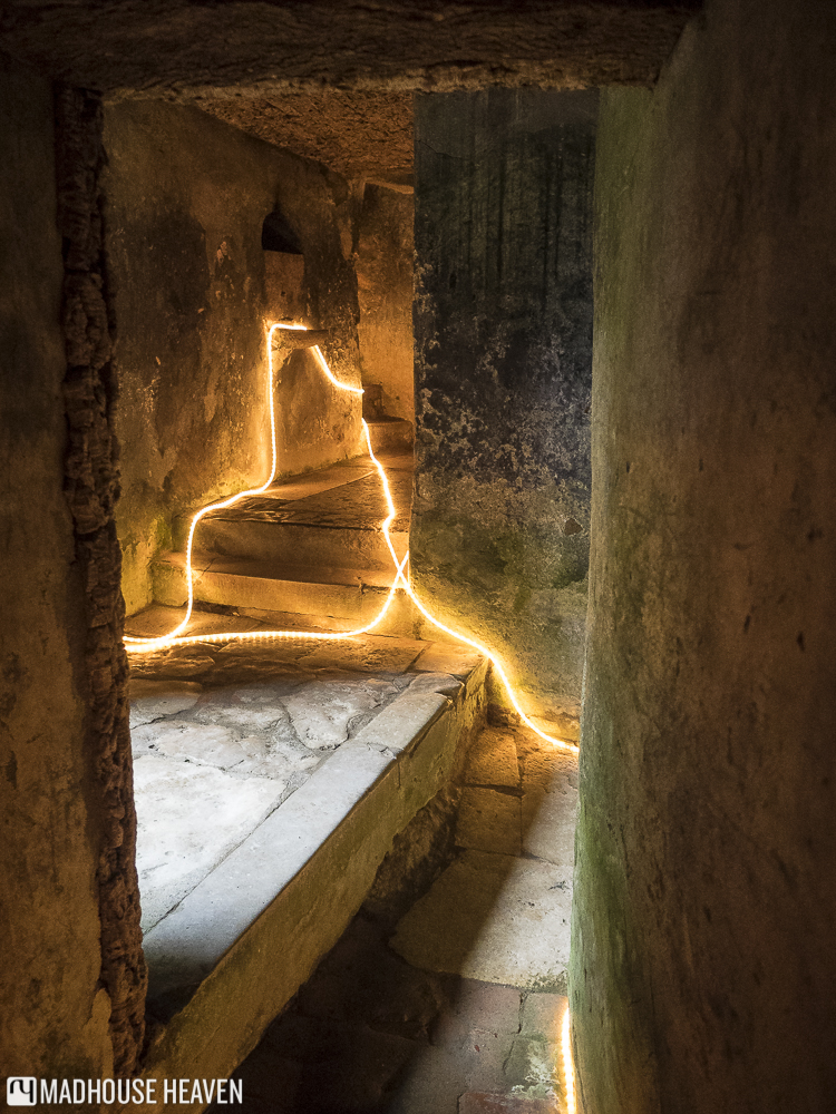 Narrow corridor lit by glowing yellow tubes, Inside the Convent of the Capuchos