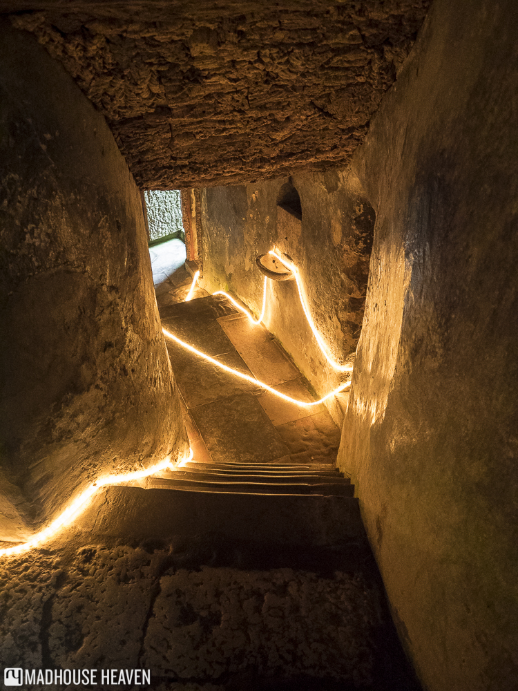 Narrow steep stairs lit by yellow fairy lights, catacombs of the Convent dos Capuchos