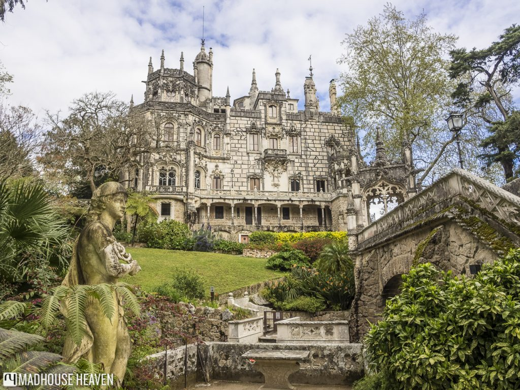 A view looking up at the palace of the Quinta da Regaleira, fronted by a grassy yard and a moss covered greek statue