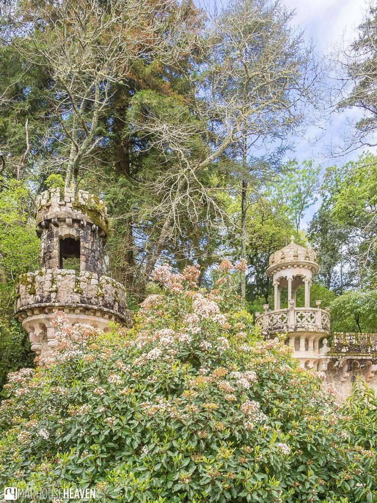 Stone towers hidden by lush vegetation in Quinta da Regeleira