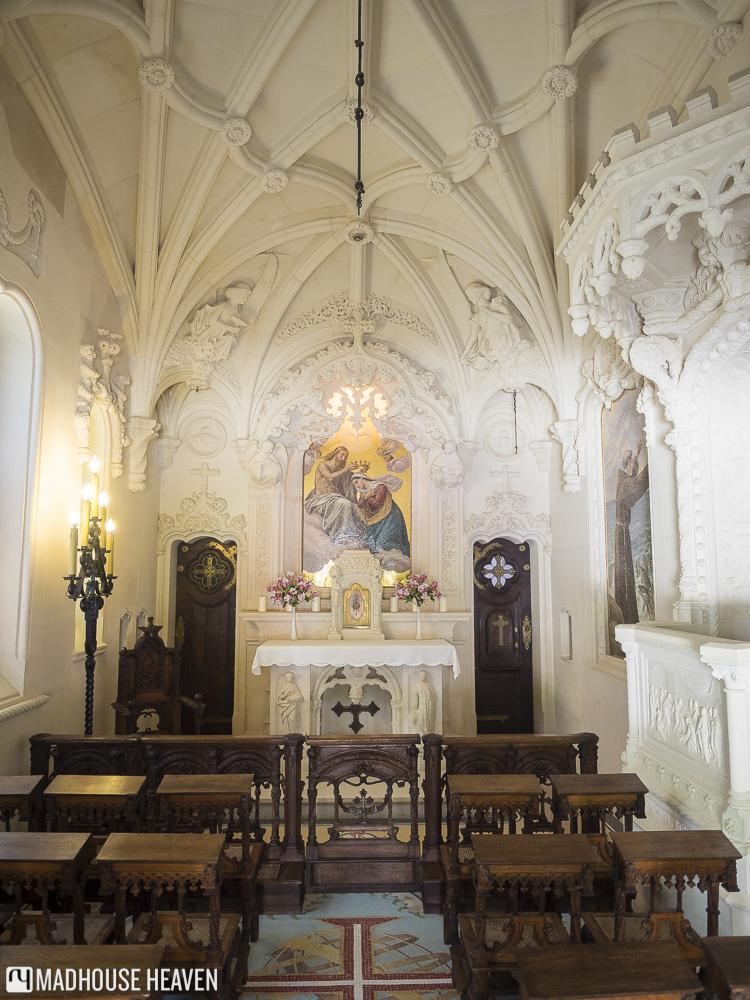 The pure white interior of the Chapel of Quinta da Regaleira, with its elegant golden alter and simple pews