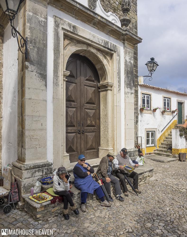 People sitting outside the Igreja de Santa Maria church, Óbidos, Portugal