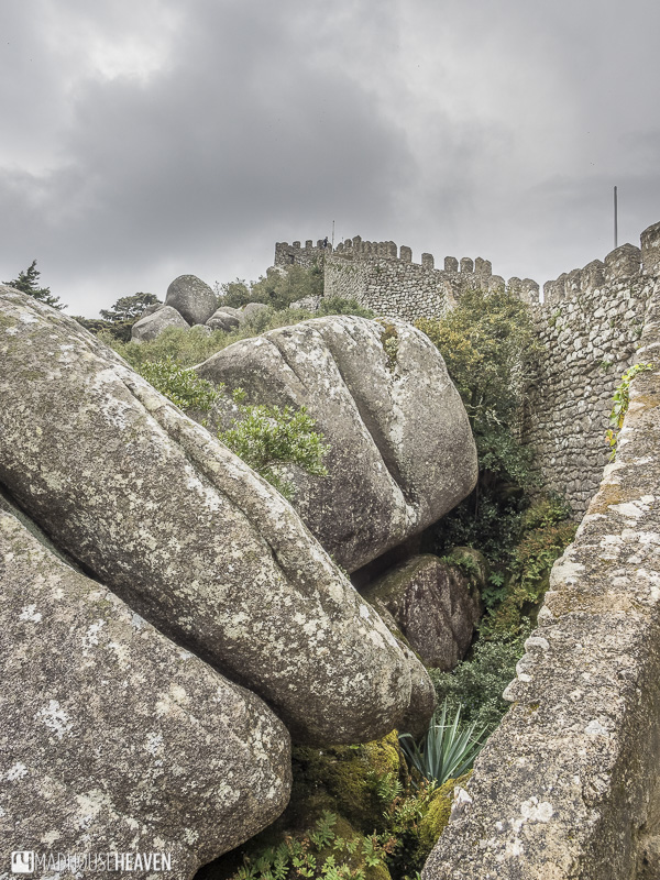 three stacked boulders surrounded by grass at the foot of the Moorish Castle Sintra