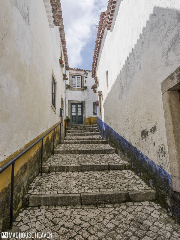 Cobblestoned alleys of Óbidos, lined with whitewashed houses adorned with yellow and blue motifs
