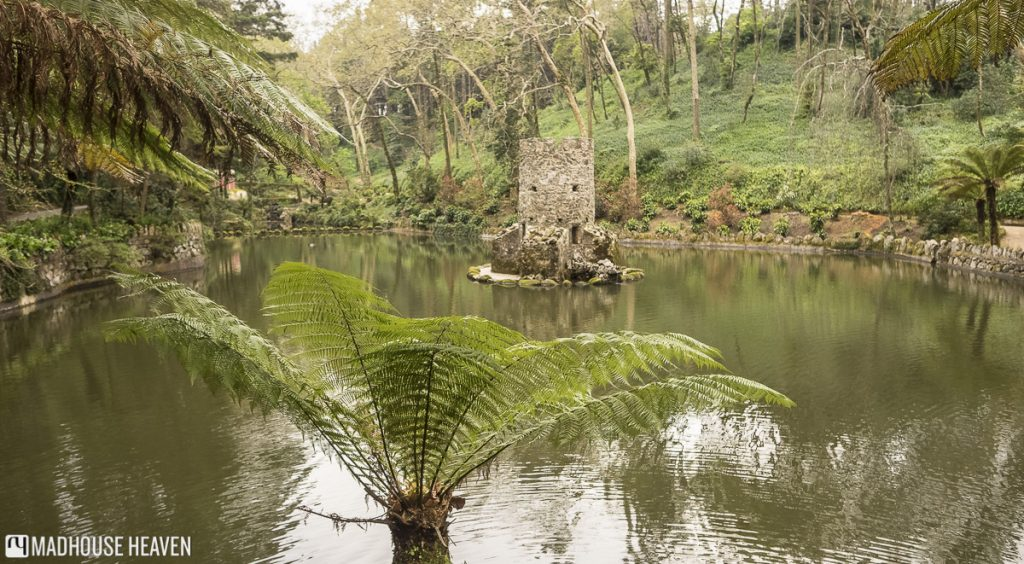 Lake in the garden of Pena National Palace with stone tower on island, Sintra, Portugal