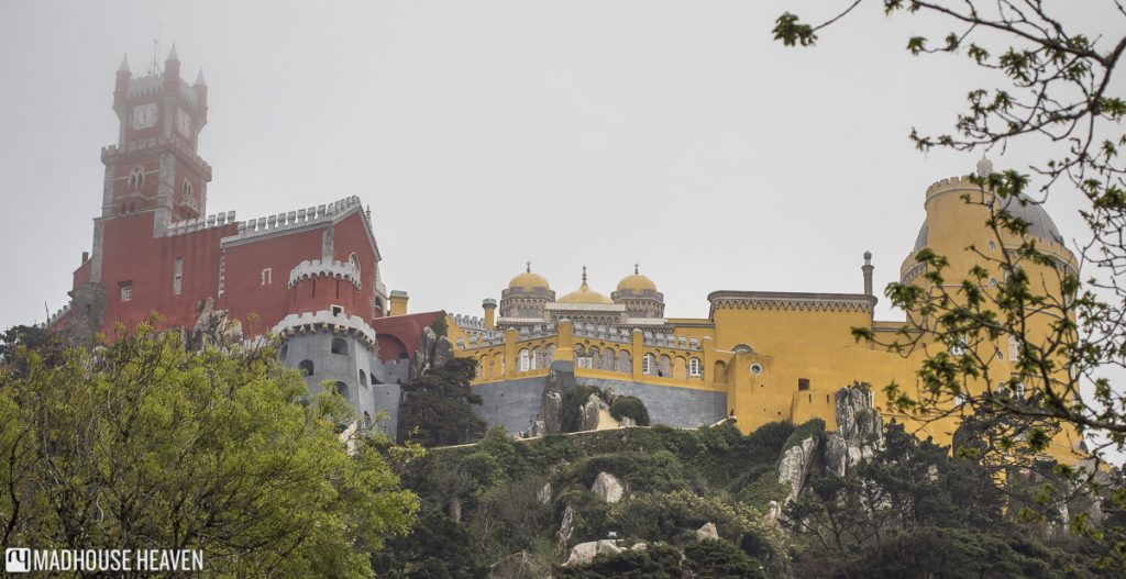 Three point perspective, red and yellow stone walls, castle rising out of the forest, Science Romanticism Pena National Palace