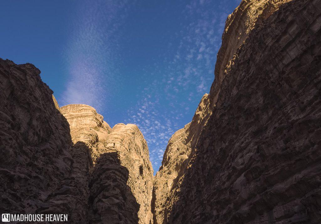 sunlight hitting top of canyon, the siq, entrance to petra, jordan travel destination