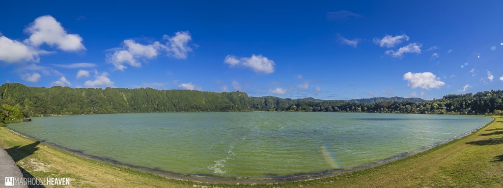 panorama of furnas lake during our day trip, with blue skies and fluffy clouds