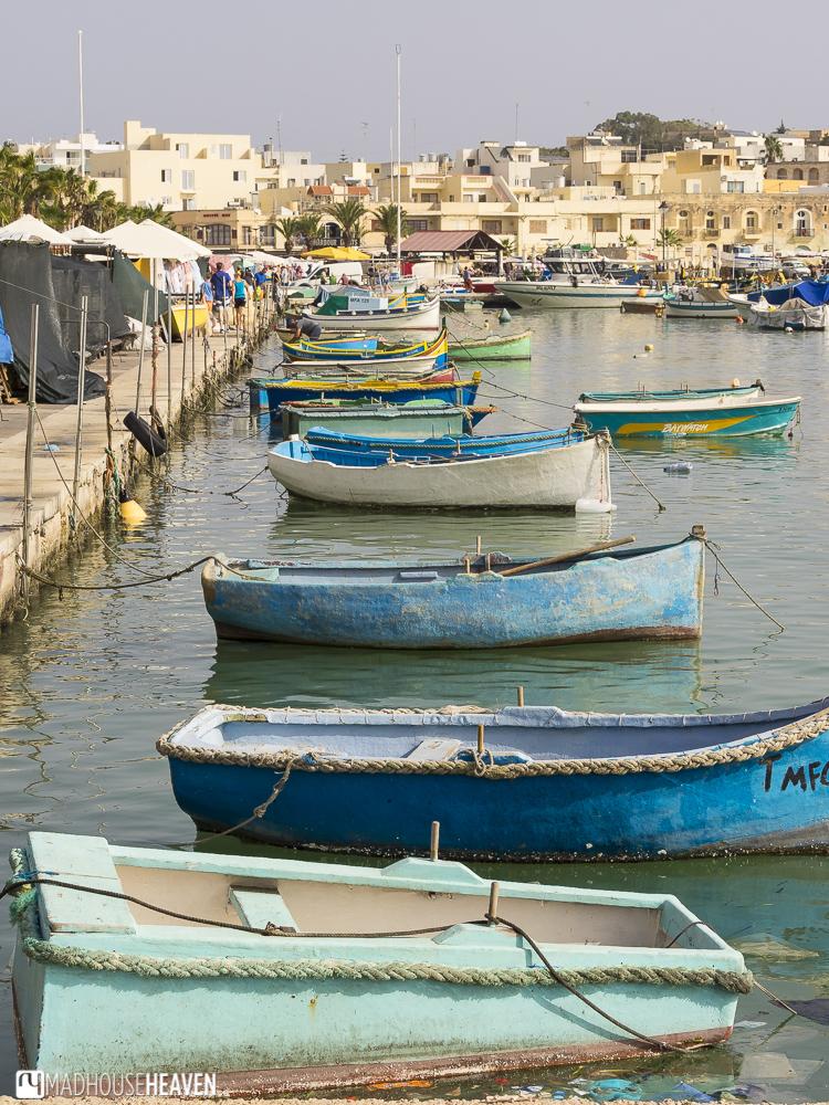 Blue boats in fishing village at Marsaxlokk Market on Sunday, Malta