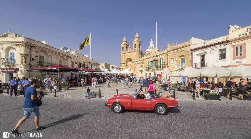 Red vintage car on the square - Marsaxlokk Market on Sunday