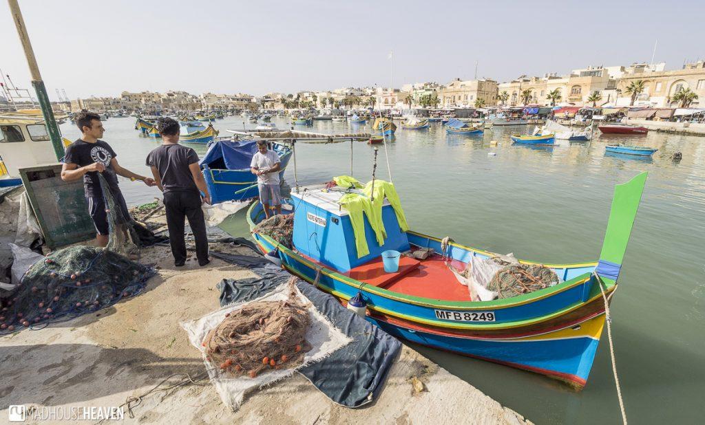 Fishermen handling piles of fishing nets on colourful boats