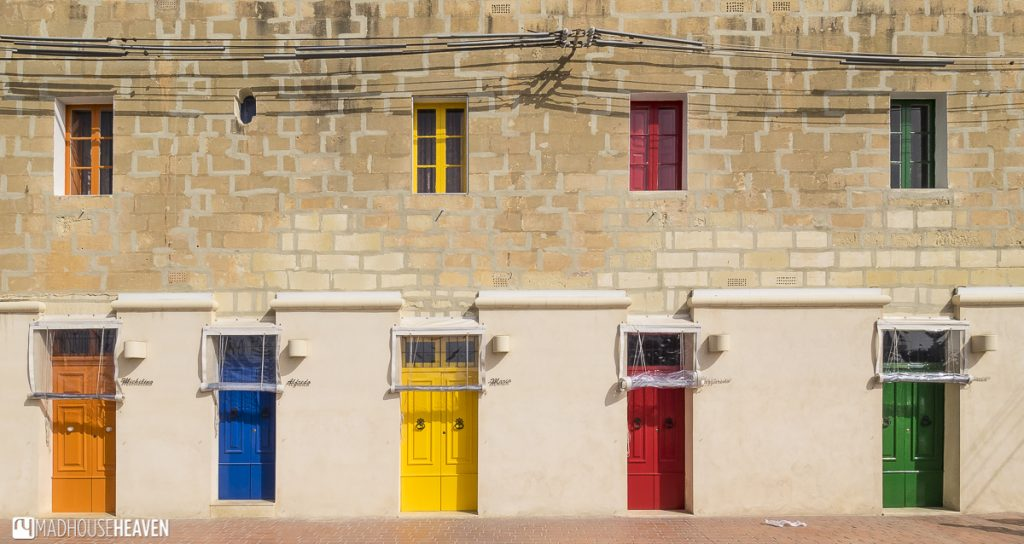 An old Mediterranean building, its stone walls bleached by the sun, with colourful doors in each of the primary colours