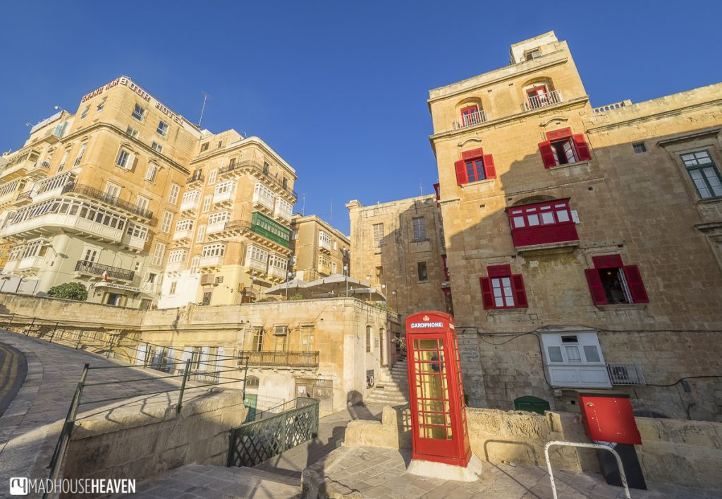 Quaint European streets in the renaissance fort city of Valletta, red british telephone box, Middle-Eastern architecture
