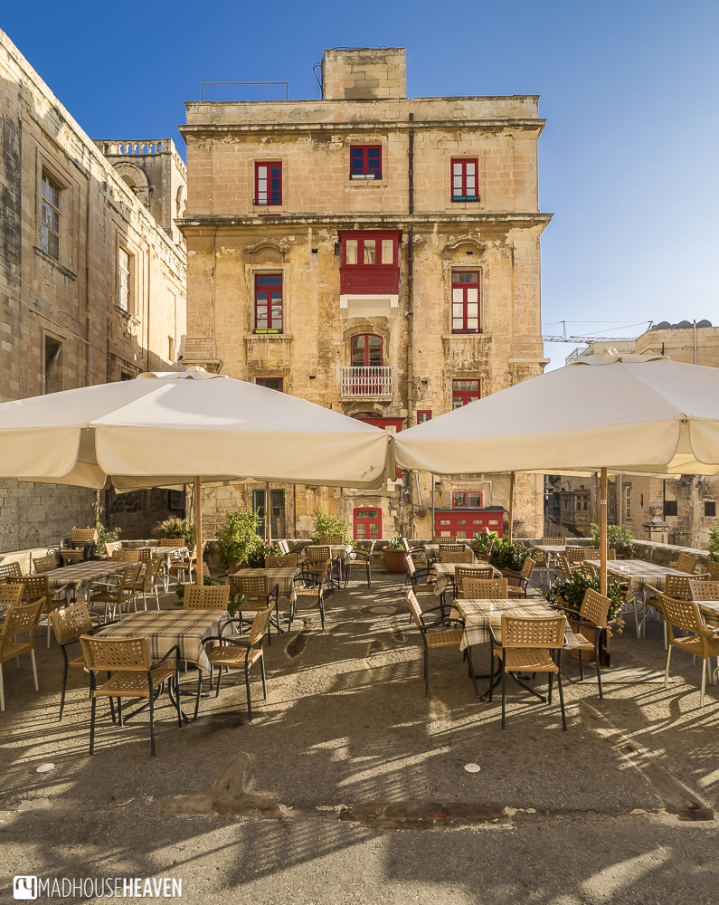 Sunny terrace near the fort walls in the old European city of Valletta, yellow stone building with red bay windows