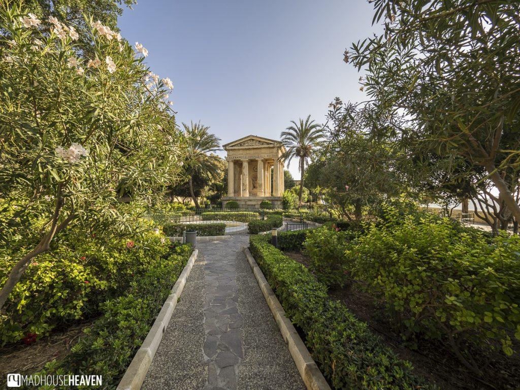 Narrow path through royal Baraka gardens, leading to a neo-renaissance gazebo, surrounded by manicured hedges, Valletta, Malta.