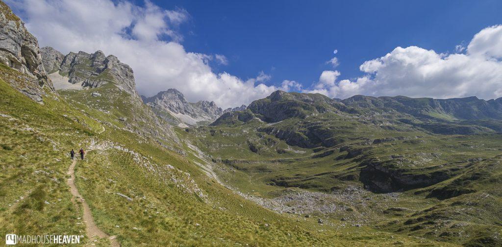 Hiking trail to Škrčko Lake cutting through rolling hills bordered by high limestone peaks - Durmitor Mountain Range, Montenegro