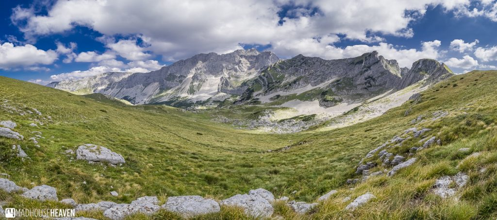 Blue skies with white clouds over rolling valley covered in green grass high up in the mountains - Skrcko Lake, Durmitor mountain hike, Montenegro