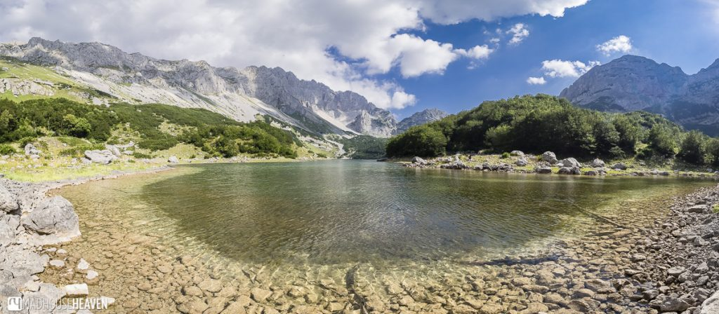 Škrčko Lake in the Durmitor Mountains, Montenegro - a mountain lake with a stone bank under a blue sky with white clouds