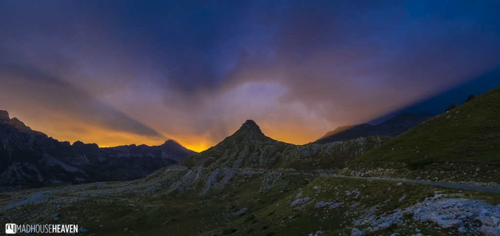 Golden rays of sunlight bursting behind the silhouette of a peak in the Durmitor mountain range at sunset - the night sky a deep indigo