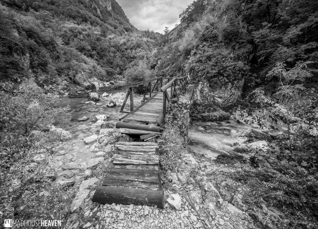 Derelict old wooden bridge across the a canyon and over a rushing river - Mrtvica Canyon, Montenegro