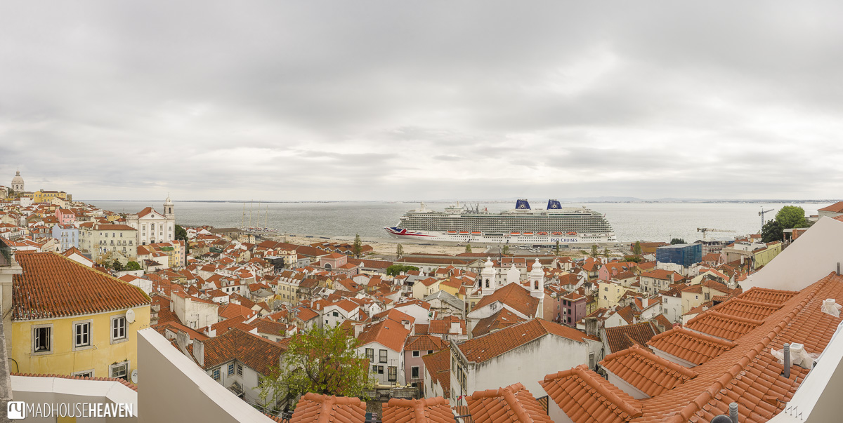 tightly packed roofs of medieval Alfama, part of Lisbon's Architectural History, in contrast with modern cruise liner in the sea
