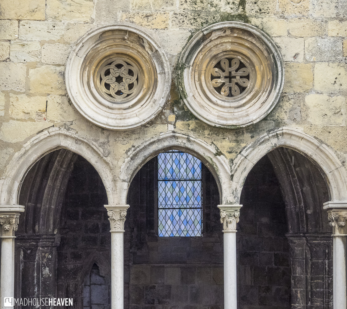 church arches with bright stained glass window against dark shadows - churches in Lisbon