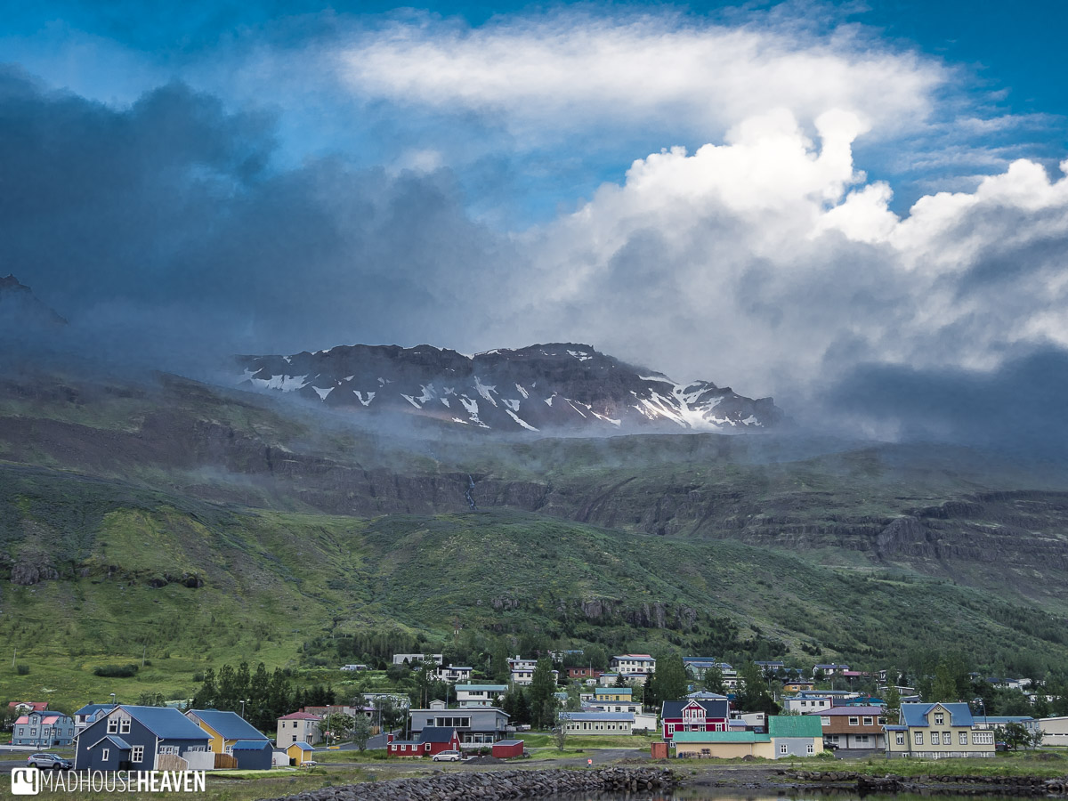 Seyðisfjörður, Iceland, cute Scandinavian village with snowy mountain in the background, epic clouds