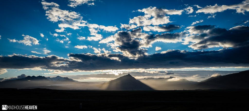 Silhouette of  Mt. Búlandstindur with the sun setting behind it and vivid blue skies above.