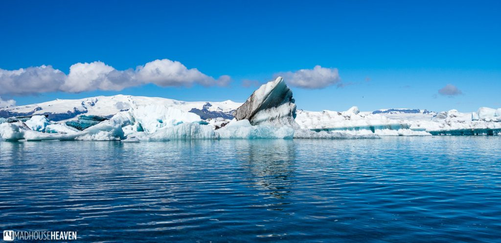 Panoramic shot of icebergs reflected in the blue waters of the Jökulsárlón Glacier Lagoon