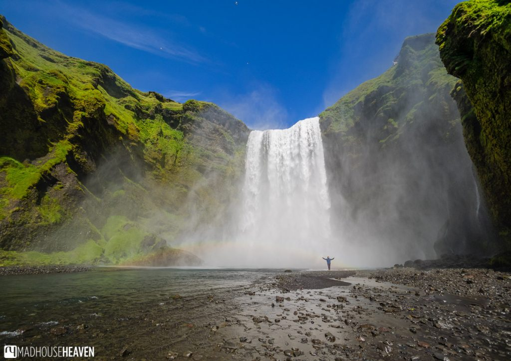 Panorama of the Skógafoss waterfall in Iceland, with one person standing in front of it