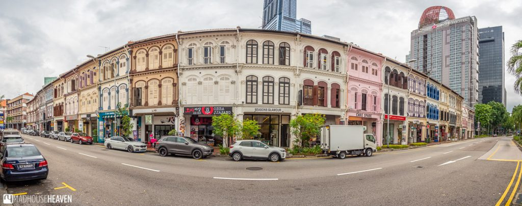 A wide angle view of a row of colourful traditional shophouses with beautiful windows and shutters