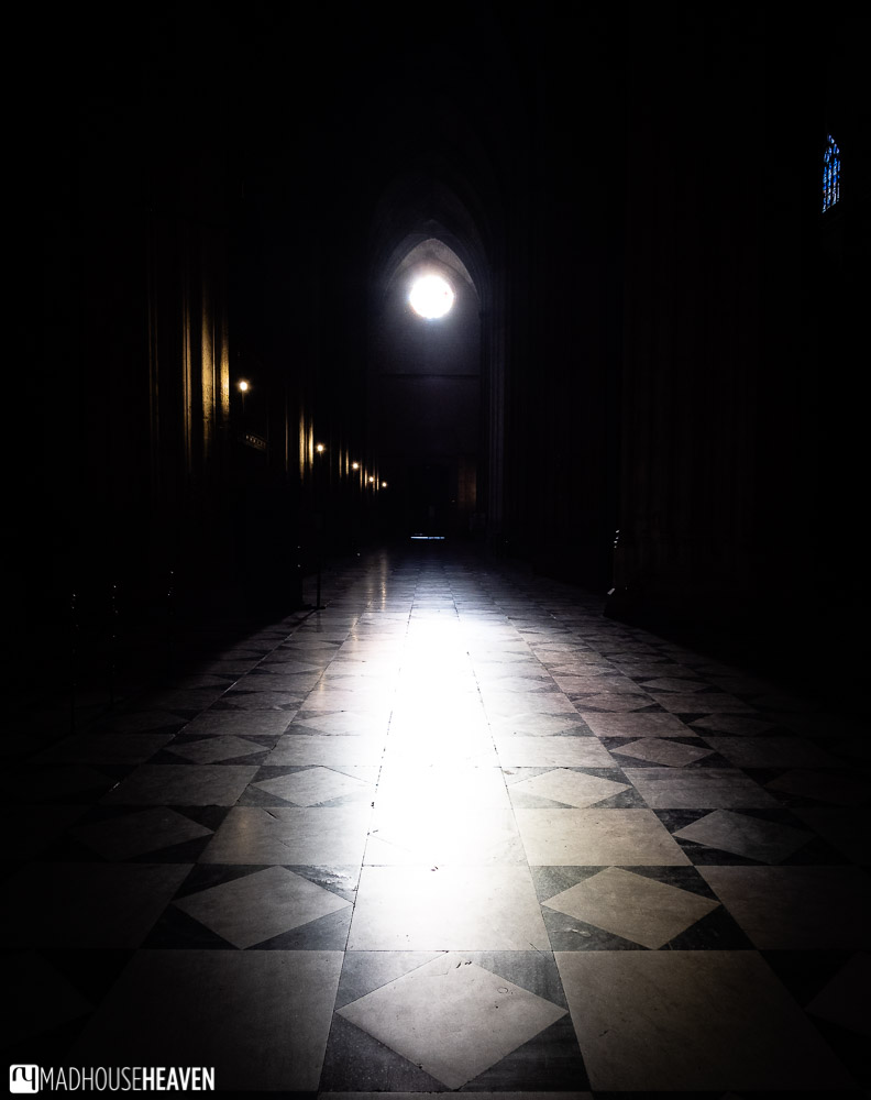 Sunlight shines through a rose window into the cavernous and dark central nave of Seville Cathedral