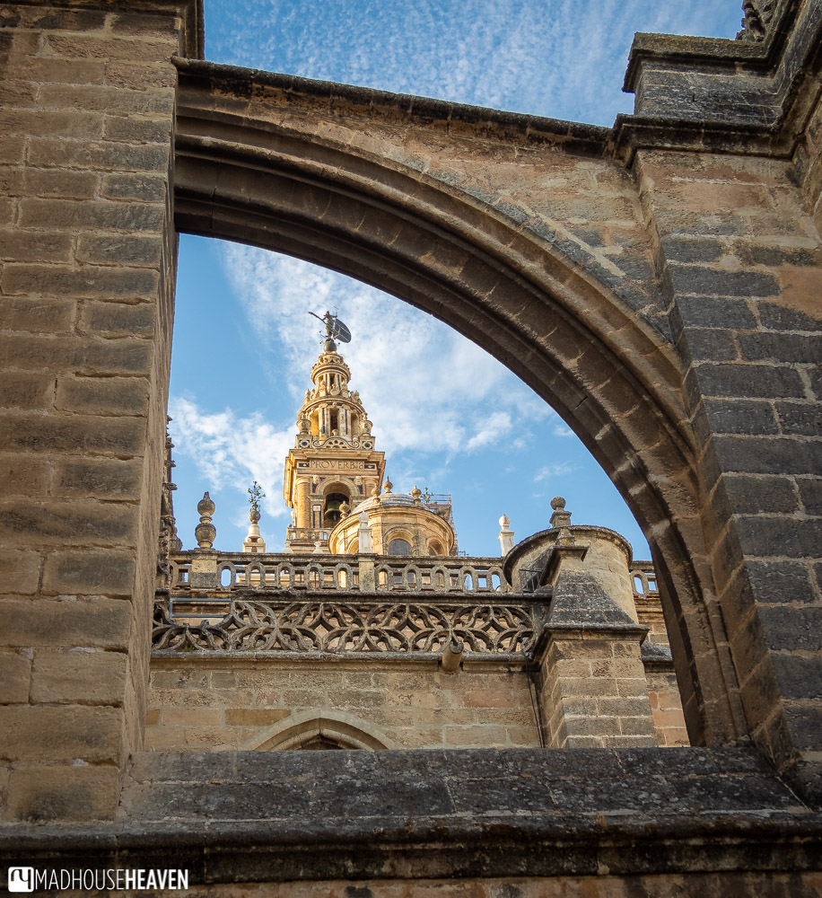 View of Giralda Tower framed by a flying buttress of Seville Cathedral