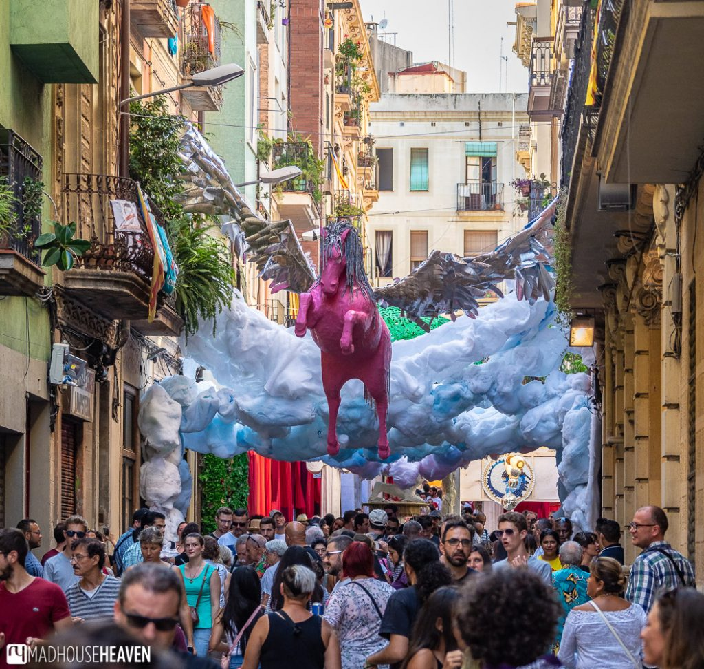 A pink paper mache unicorn hanging over a street in Barcelona