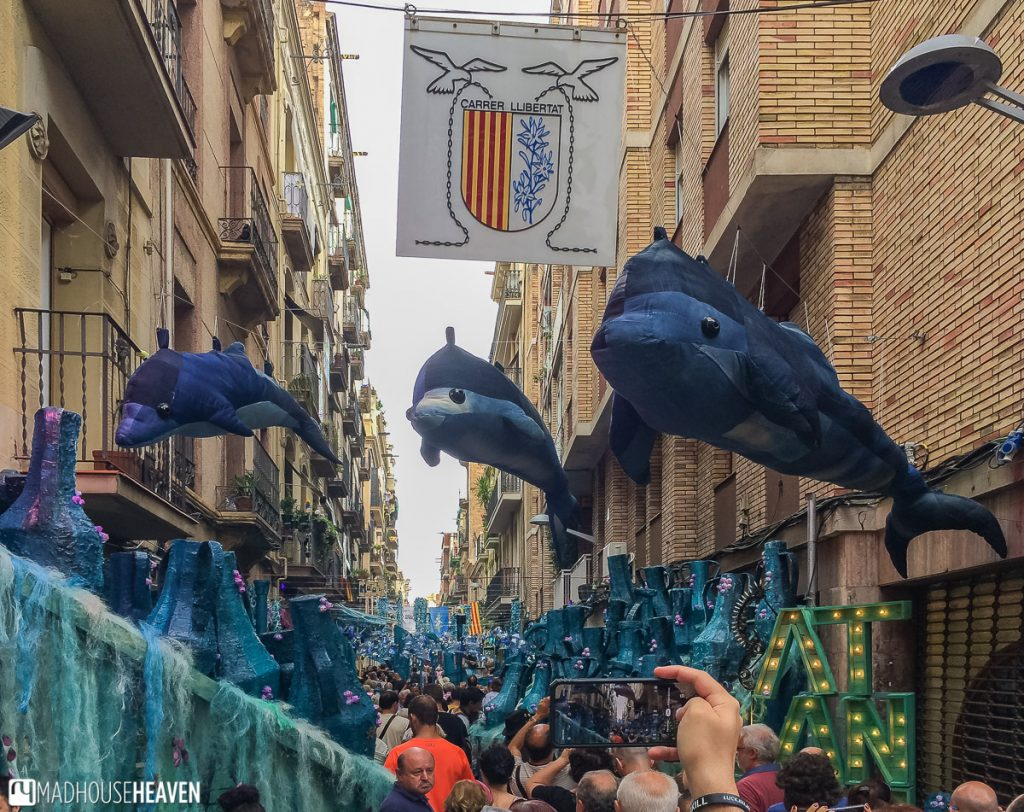 Stuffed dolphins hanging over a street and a crowd of people