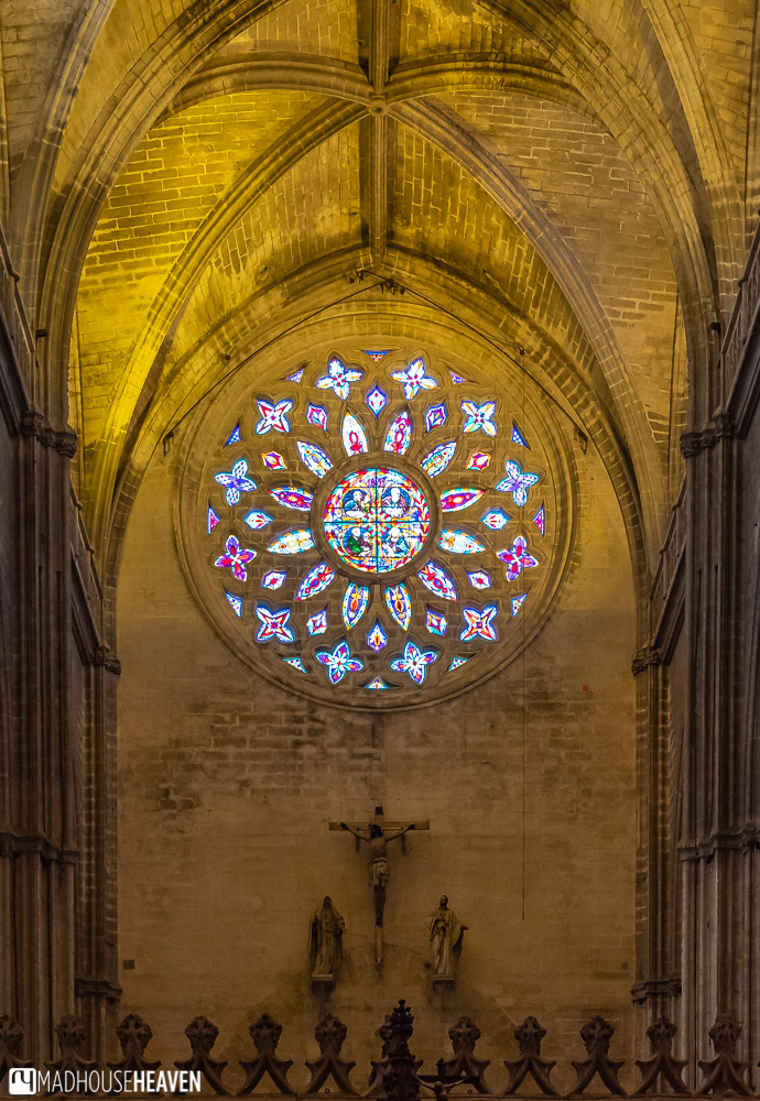 The rose window of the Seville Cathedral with its many coloured glass pieces is lit by the afternoon sun