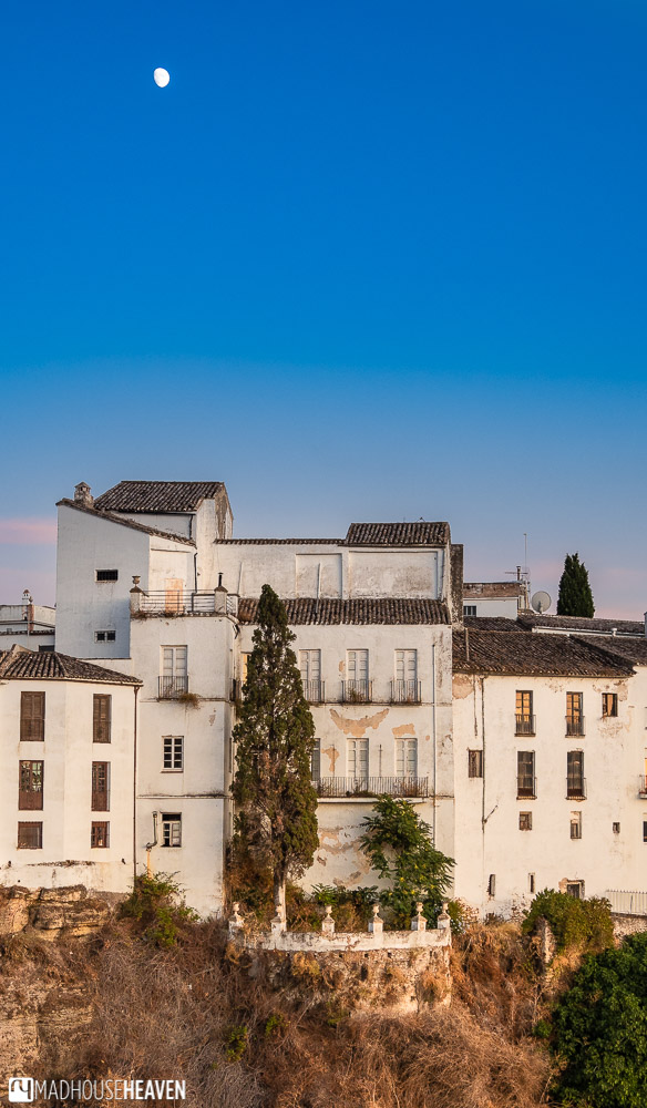An abandoned house in the old town of Ronda at sunset, with a long deserted overgrown terrace featuring a very tall poplar