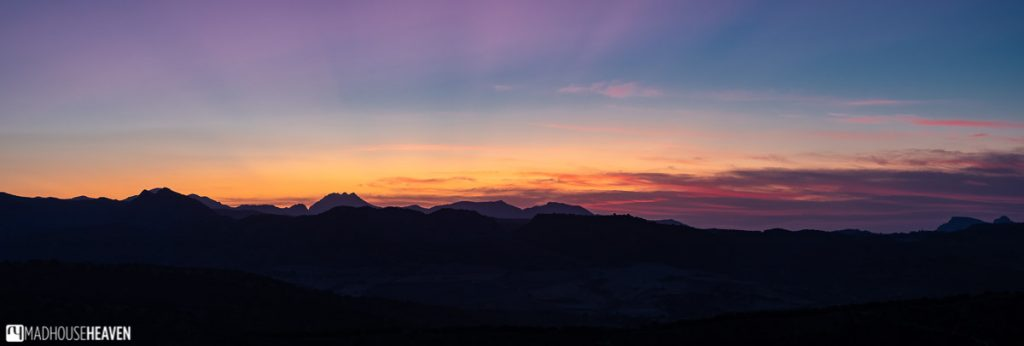 Panorama of a sunset behind a distant mountain range, turning the skies yellow, orange and purple