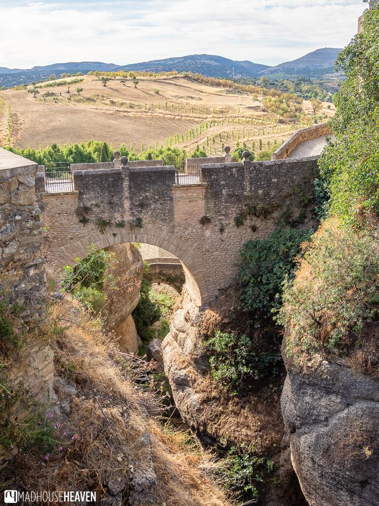 The Puente Árabe bridge is seen through the arch of the Puente Viejo bridge