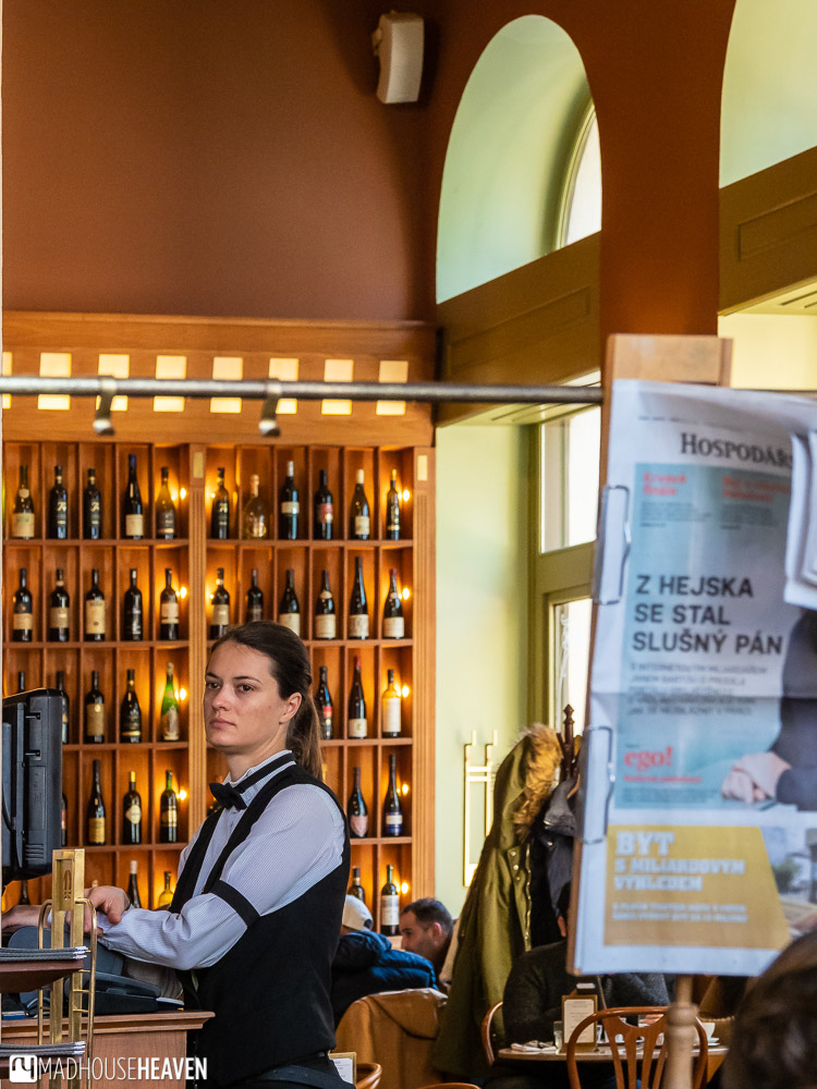 A waitress standing in front of a wall of wine and a Czech language newspaper, in a café in Prague