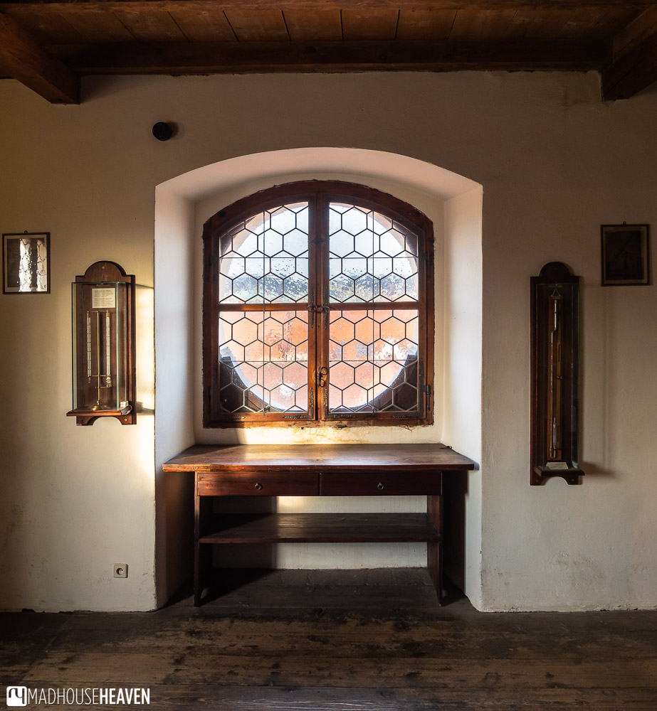 Sunlight shines through a circular window, lighting up instruments of measurement hanging on a wall the the Klementinum
