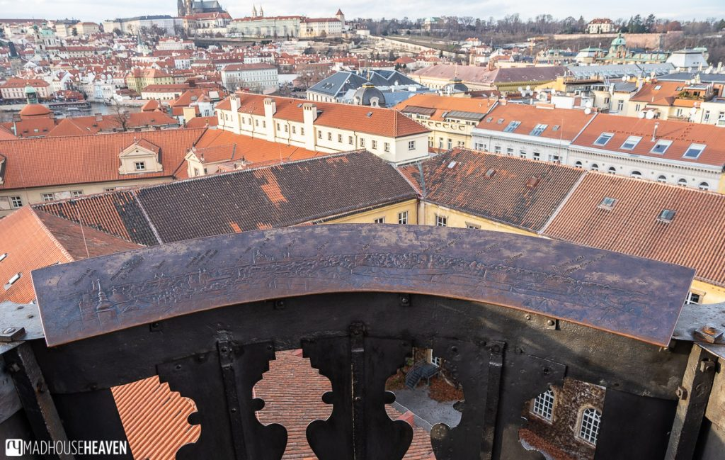 An etched panoramic map of Prague is attached to the banister in one of the corners of the Astronomical Tower