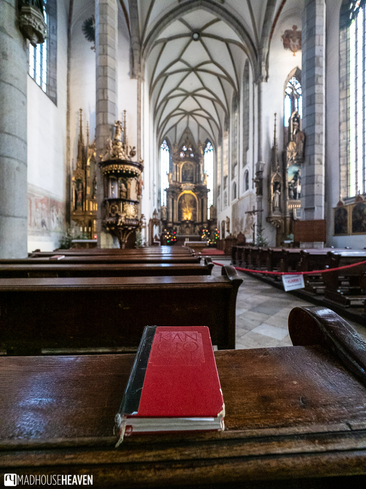 A red hymn book on a plain wooden pew in the simple Gothic interior of the St. Vitus church