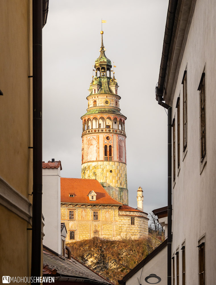 Little Castle and the Castle Tower, elegantly Renaissance in design, rise above Český Krumlov, seen through a narrow street