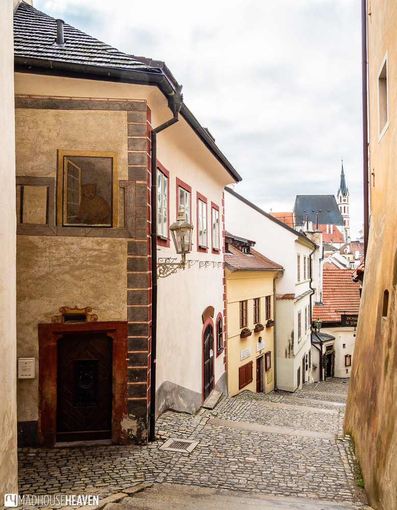 Mural of the Cesky Krumlov bear painted on a house at the top of the castle steps. The bear is looking out towards pedestrians climbing the stairs.