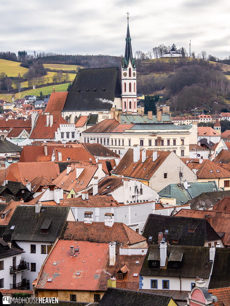 A beautiful Gothic church in Cesky Krumlov is surrounded by red roofed houses from the medieval era