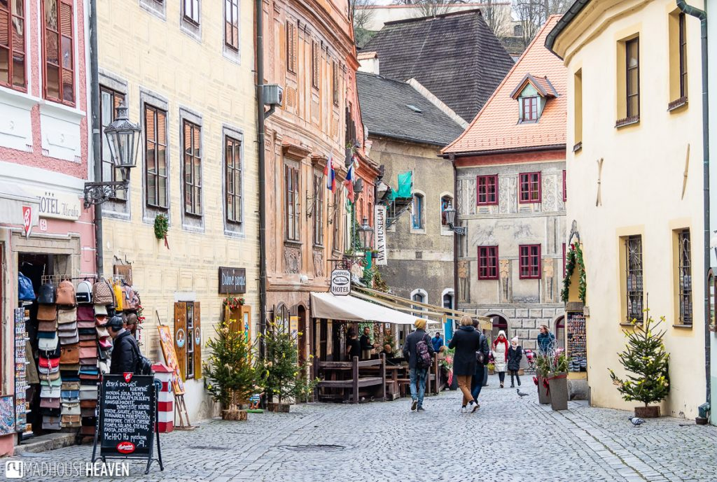 A cobblestone street in Cesky Krumlov, with shops and bars, lined with historic buildings