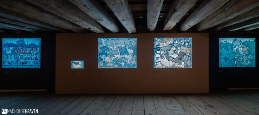 Ego Schiele paintings of Český Krumlov on display in a low wooden gallery