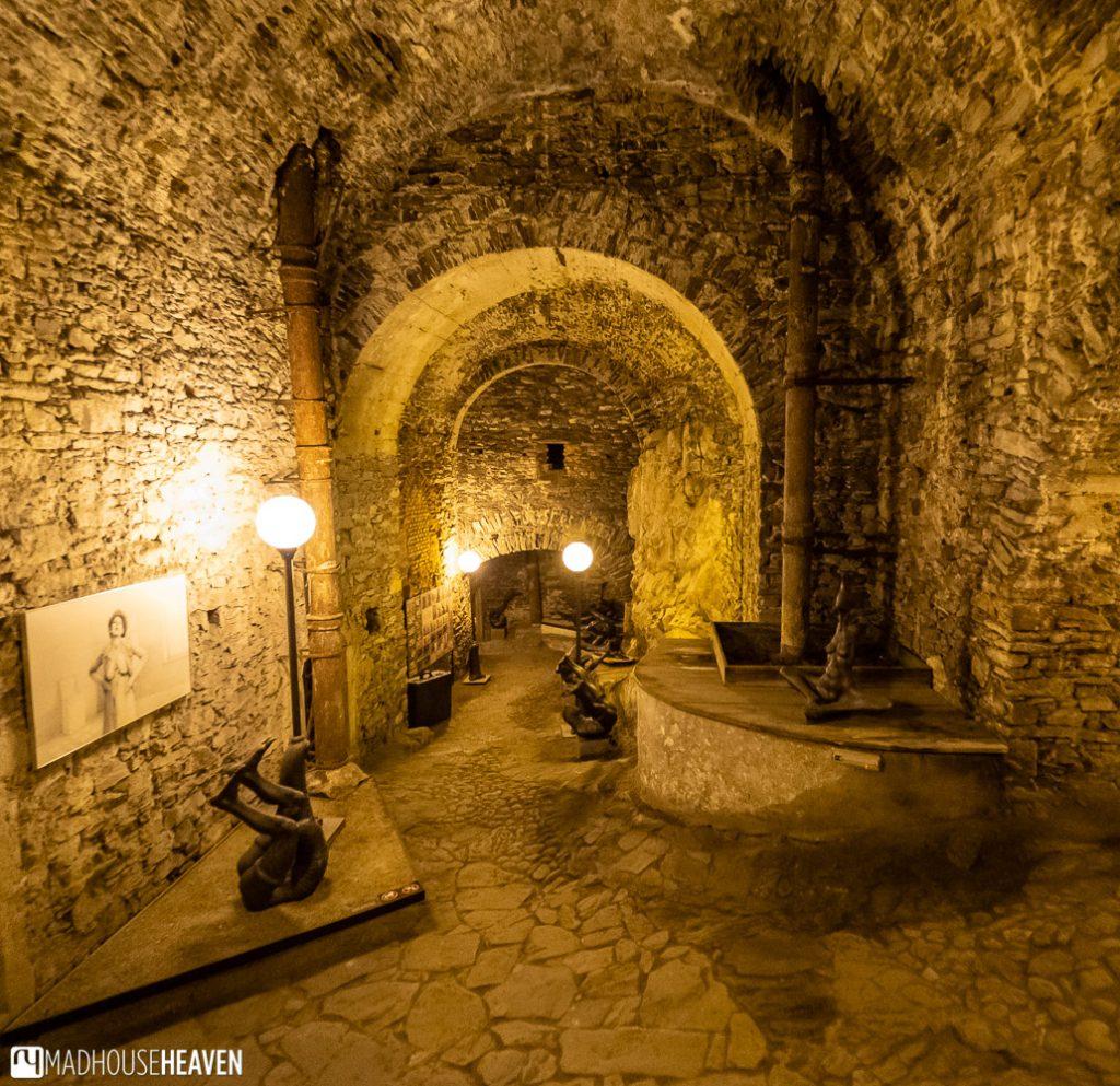 Stone castle cellar in the Český Krumlov castle, lit by warm yellow lamps